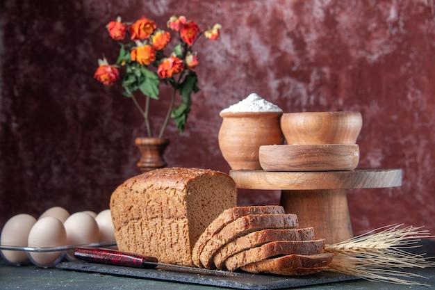 혼합 색상 고민 배경에 나무 보드 계란에 어두운 색상 트레이 밀가루 오트밀 메밀에 검은 빵 조각의 상위 뷰