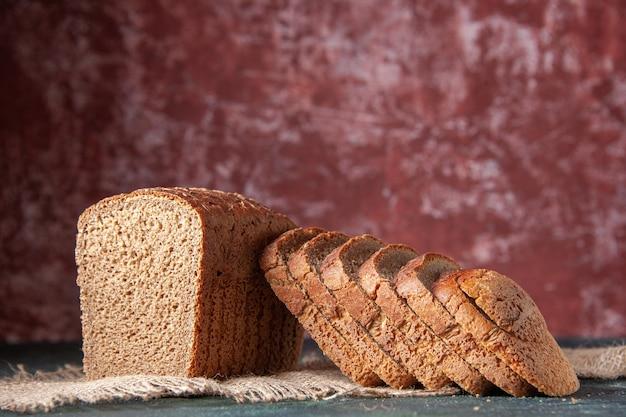 栗色の背景のヌード色のタオルの上の黒いパンのスライスの上面図