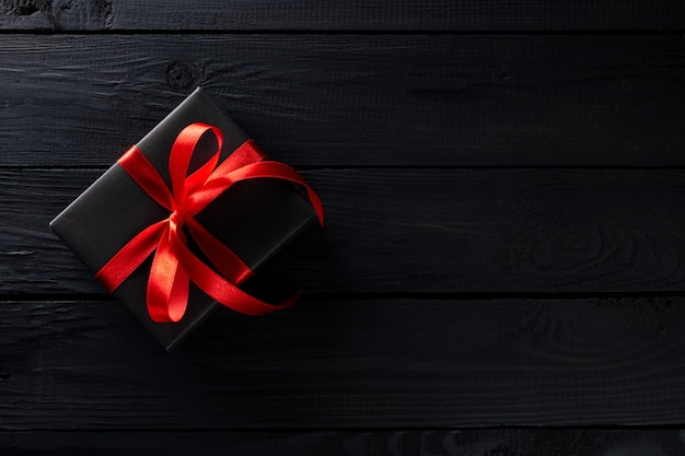 Вид сверху черных рождественских коробок с красной лентой на черном деревянном