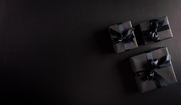 Вид сверху черных рождественских подарочных коробок с черной лентой на черной стене с копией пространства