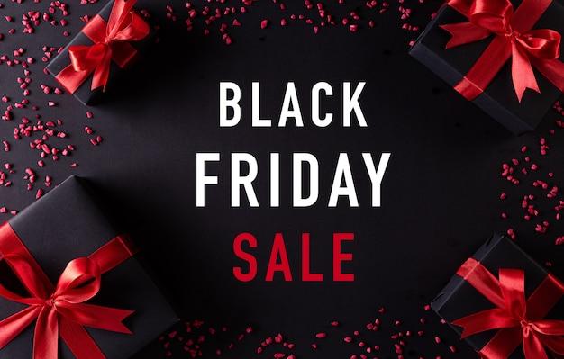 Вид сверху черных рождественских подарочных коробок с красной лентой композиция bkack friday sale