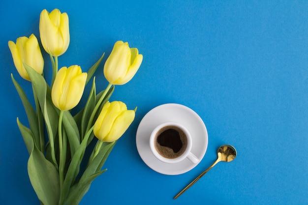 파란색 표면에 블랙 커피와 노란색 튤립의 상위 뷰