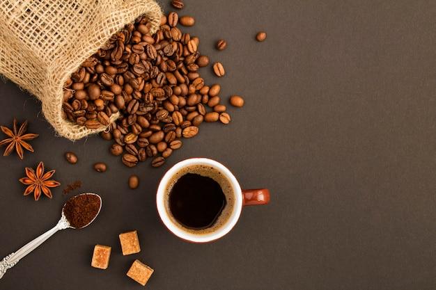 Вид сверху черного кофе в коричневой чашке и кофейных зерен на темном фоне