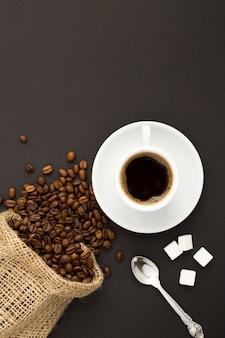 Вид сверху черного кофе в белой чашке и кофейных зерен на темном фоне