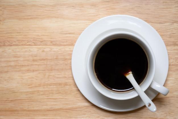 コピースペースと木製の背景に白いカップのブラックコーヒーの上面図。