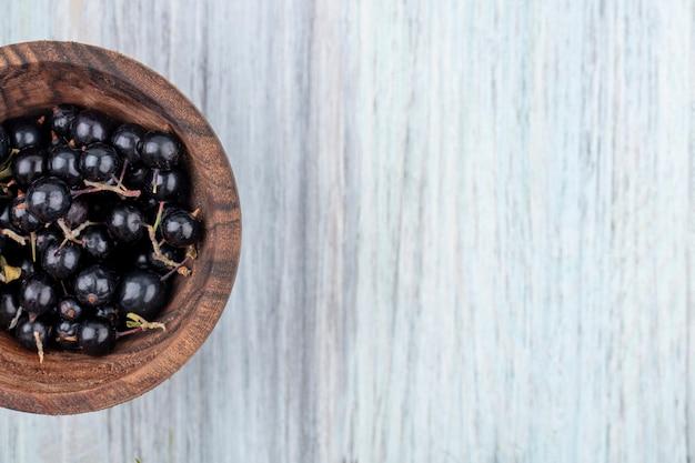 Вид сверху черной смородины в миске на серой поверхности