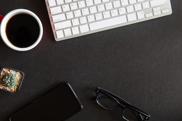 사무용품 및 장치가있는 검은 책상 사무실의 상위 뷰