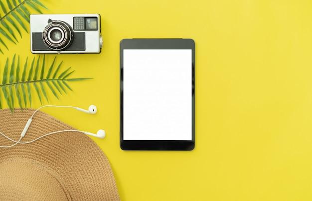 黄色の背景に黒のデジタルタブレットとカメラと帽子の平面図です。夏の休日や旅行のコンセプトです。