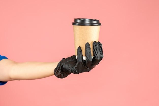 パステル ピーチの背景においしいコーヒーのカップを持っている手を身に着けている黒い手袋のトップ ビュー