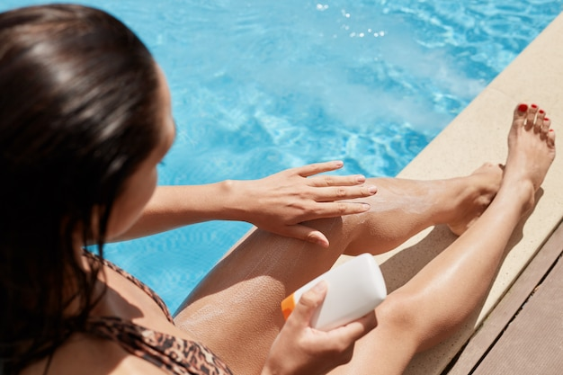 スイミングプールのそばでリラックス、手で彼女の足に触れる、日焼け止めクリームを適用する、片手でチューブを保持、ヒョウスイミングスーツを着ている黒い髪のスレンダー女性の平面図。残りのコンセプト。