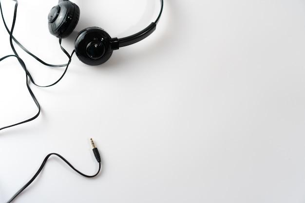 白またはパステルカラーの背景に黒のヘッドフォンの平面図です。