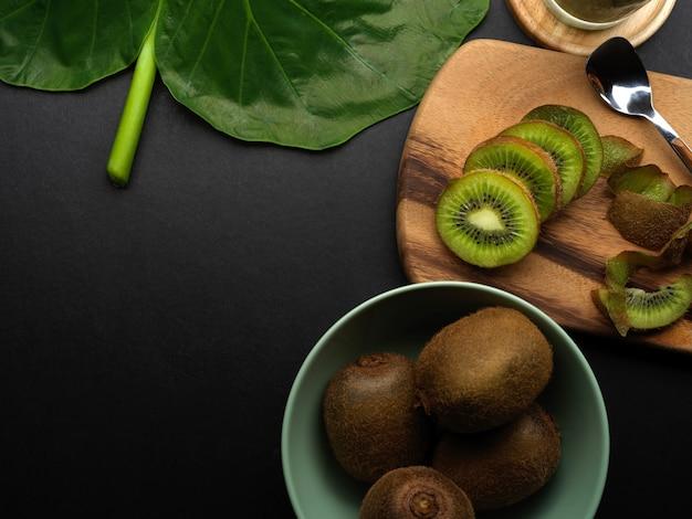 新鮮なキウイフルーツ、緑の葉とコピースペースと黒いキッチンテーブルの上面図
