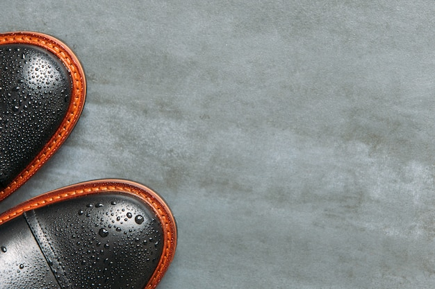 Вид сверху черные кожаные мужские сапоги с каплями воды на темно-синем фоне гранж, копией пространства, плоской планировке. теплая обувь для осенней погоды.