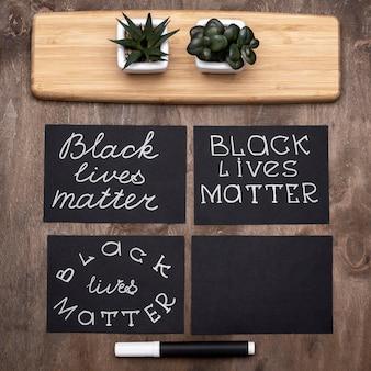 Вид сверху на черные карты материи жизней с растениями и ручкой