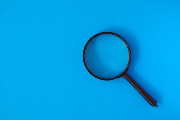 블루 파스텔 표면에 검은 돋보기의 상위 뷰. 더 나은 시력을위한 루페. 최소한의 디자인. 탐구.