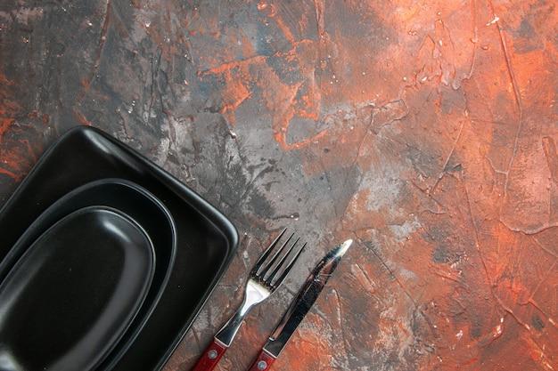 Вид сверху черных овальных и прямоугольных тарелок, вилки и ножа на темно-красной поверхности