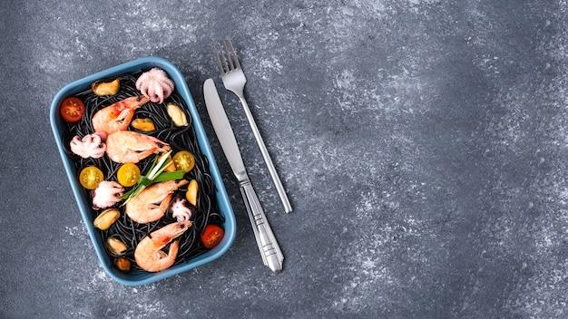 シーフードの黒いパスタの上面図-エビ王、ムール貝、タコ、チェリートマト、青いプレート、フォーク、ナイフ、灰色の背景、コピースペース