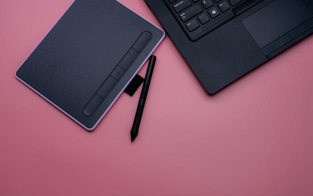 Вид сверху черной ручки мыши, цифрового планшета и ноутбука для графического дизайна на розовом фоне. вид сверху графического планшета. гаджет для графического дизайнера. bluetooth и беспроводное устройство.