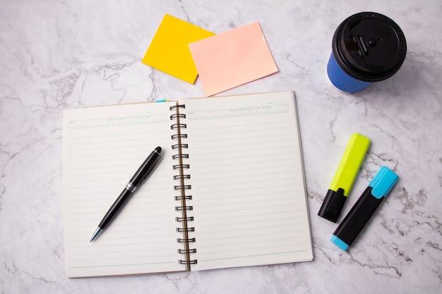 Вид сверху черной ручки на открытой книге, пустой странице записной книжки, желтой и синей ручке маркера, липкой записке и синей чашке кофе на белом мраморном столе. мраморный офисный стол. шаблон. задний план.