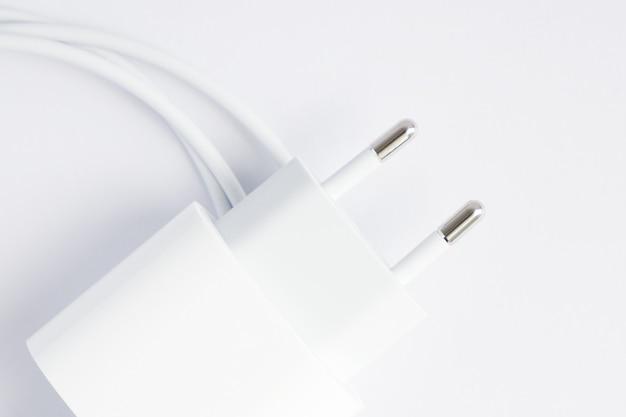 흰색 바탕에 검은색 전화 ac 충전기와 usb 케이블의 상위 뷰.