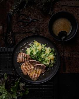 구운 스테이크와 완두콩과 삶은 감자와 검은 접시의 상위 뷰