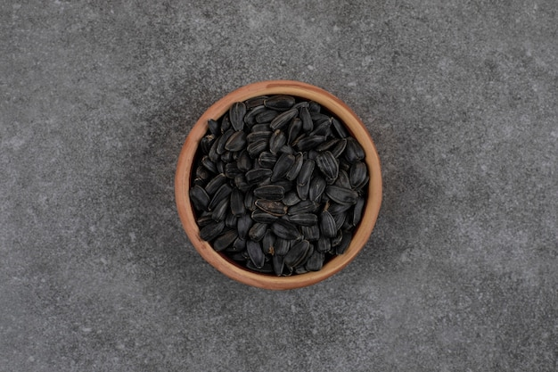회색 표면에 검은 해바라기 씨의 상위 뷰