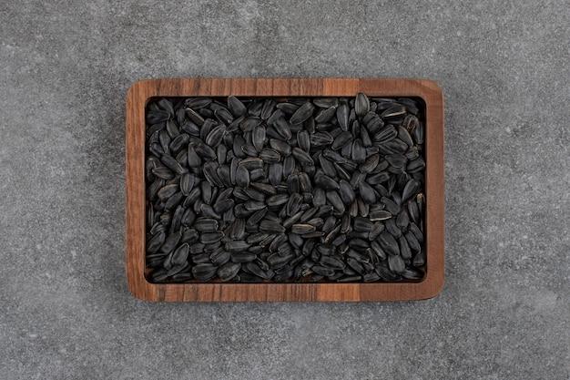 회색 표면 위의 나무 접시에 있는 검은 해바라기 씨의 상위 뷰