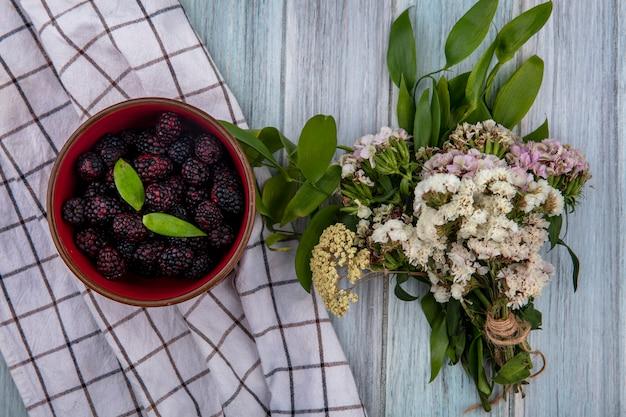灰色の表面に白い市松模様のタオルの上に花の花束をボウルにブラックベリーのトップビュー