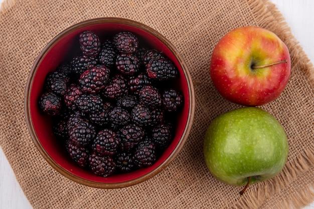 Вид сверху ежевики в миске с яблоками на бежевой салфетке