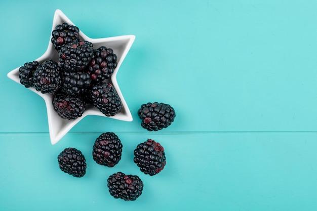 Вид сверху ежевики в блюдце в виде звезды на голубой поверхности
