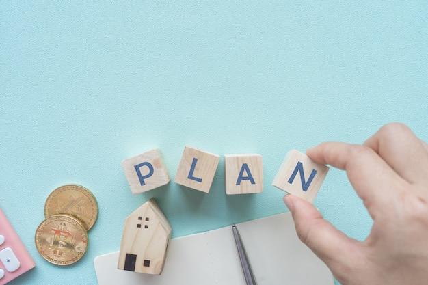 Взгляд сверху пустой предпосылки пастельного цвета copyspace с калькулятором, крошечной домашней моделью, кредитной карточкой, ручкой и словом плана на деревянном кубе как рамка. план денег состоятельный, образ жизни.