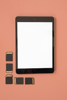 Top view of blank digital tablet with memory cards over orange background