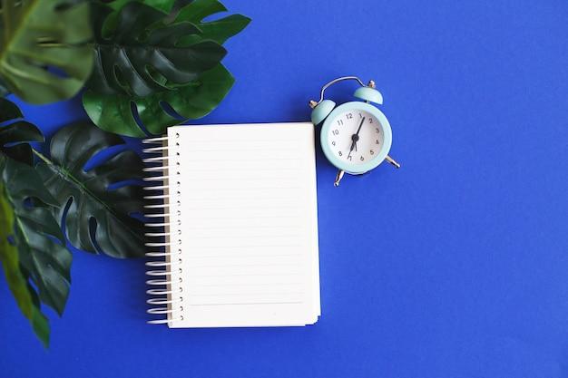 Вид сверху пустой бумажный будильник и лист монстера на синем фоне