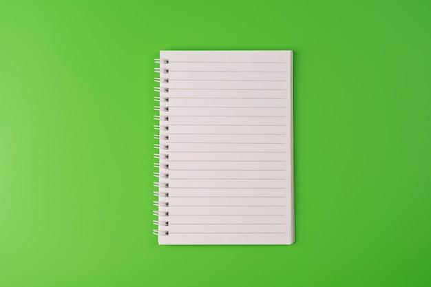 Вид сверху пустой бумаги для заметок на зеленом фоне снова в школу и концепцию образования copyspace