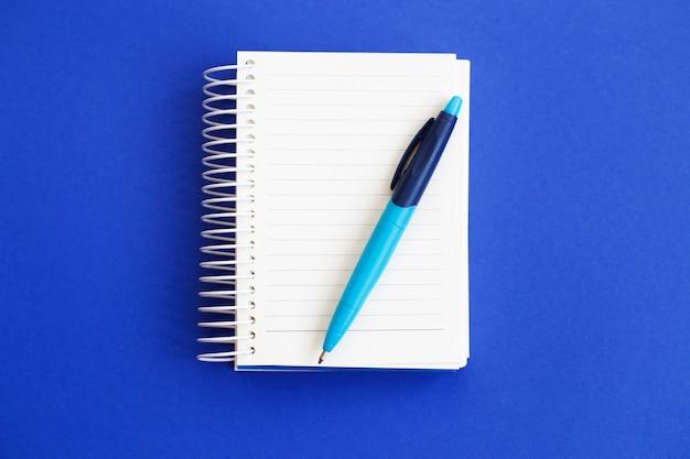 Вид сверху пустой бумаги для заметок с ручкой на синем фоне