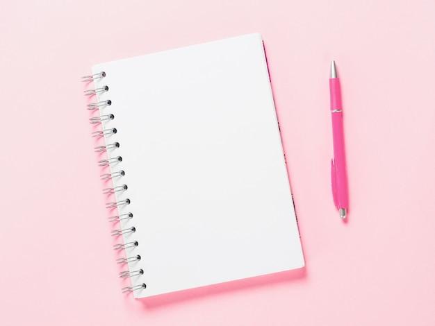 Вид сверху пустой записку с ручкой на розовом фоне