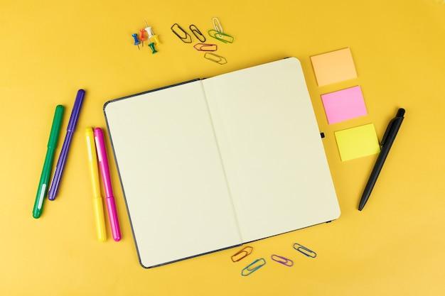 Вид сверху пустой тетради и школьных принадлежностей, таких как цветные маркеры, наклейки и клипсы на желтом фоне, место для текста.