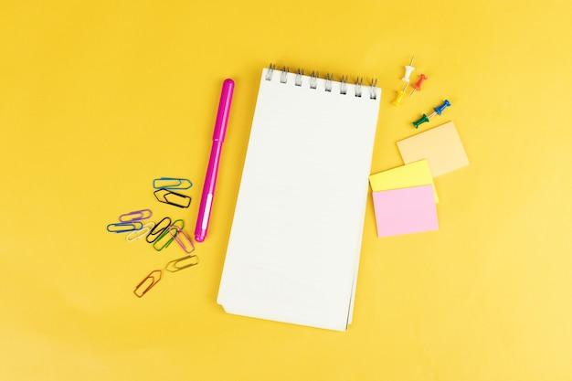 Вид сверху пустой тетради и школьных принадлежностей, таких как цветные маркеры, наклейки и клипсы на желтом фоне.