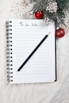 흰색 섬유 린넨 식탁보에 목록 및 크리스마스 장식을 할 수 있는 빈 노트북의 상위 뷰