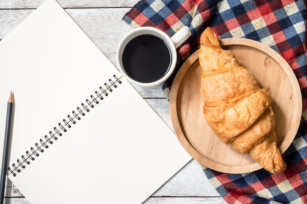 木製のテーブルの背景に鉛筆、クロワッサンとコーヒーと空のノートのトップビュー。