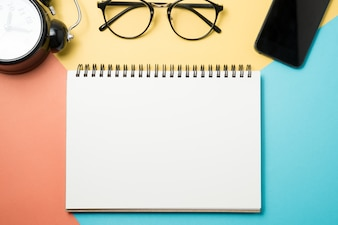 Top view of blank notepad, cellphone and glasses on pastel color background