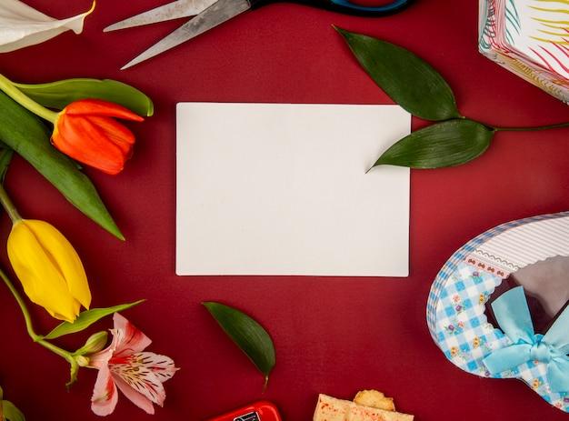 赤いテーブルに白紙のグリーティングカードとハート型のギフトボックスとアルストロメリアの花とチューリップの平面図