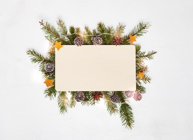 Вид сверху чистый лист бумаги с еловыми ветками