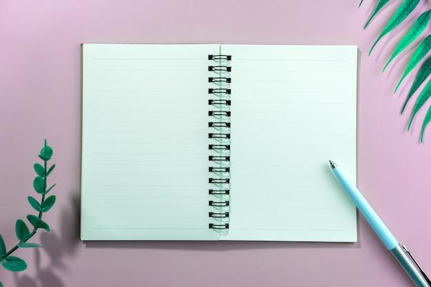 空白の白いノートブックとフレームとして熱帯の葉のペンの平面図です。