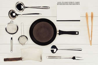Top view of blank textbook, frying pan, butcher axe and kitchen utensils on white wooden t