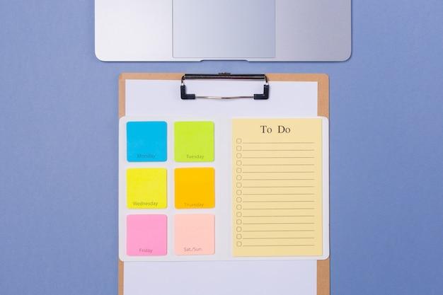 밝은 자주색 배경에 평평한 누워 주 및 노트북에 대 한 빈 할 일 목록의 상위 뷰. 공간을 복사하십시오. 자유 공간. 시간표. 시간표.