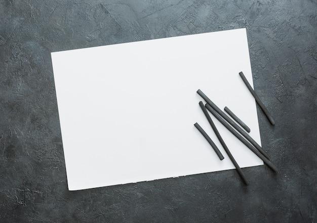 빈 흰색 시트와 천연 나무 숯 스틱의 상위 뷰
