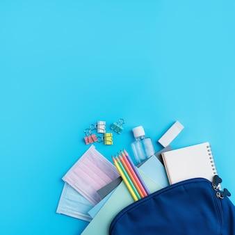 파란색 테이블 배경 위에 학교 문구류가 있는 파란색 배낭의 맨 위 보기, 다시 학교 디자인 개념으로 돌아갑니다.