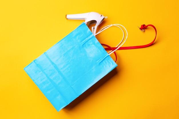 黄色の背景にスタイリッシュな靴と赤帯の青いショッピングバッグの上面図。ファッションとデザイン、ショッピングのコンセプト