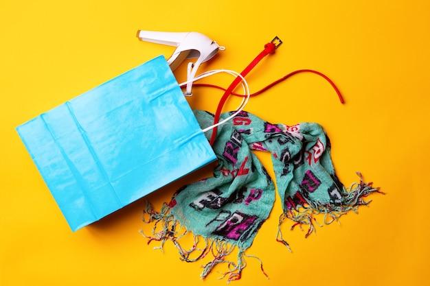 Вид сверху синей хозяйственной сумки со стильной обувью, шарфом и красным поясом на желтом фоне. понятие моды и дизайна, шоппинг